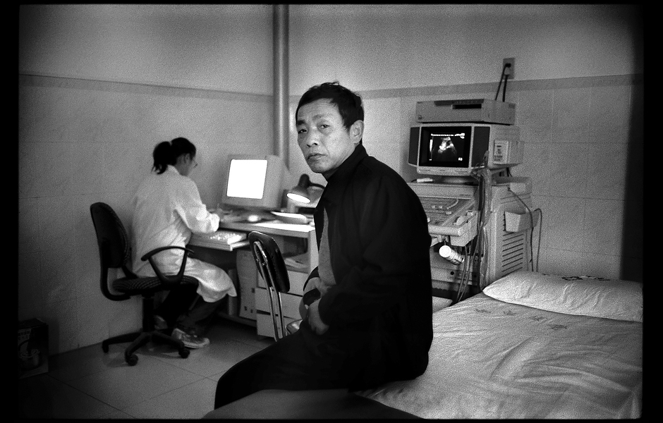 Shi Dage waits on a hospital bed to receive a liver exam. Without appropriate monitoring or treatment, one in four people infected with chronic hepatitis B will die from liver cancer or liver failure. Henan, China