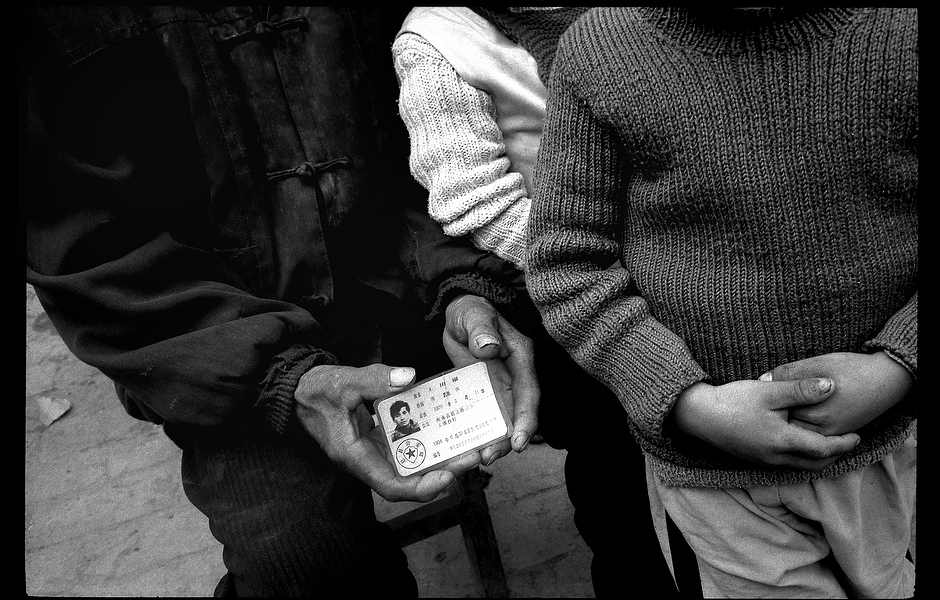 Wang Dage's father and children stand next to his ID card. Approximately 100-120 million Chinese are infected with the hepatitis B virus, yet due to a lack of resources and the social stigma that has been associated with the disease, people are unaware of the severe public health risk it poses. Henan, China