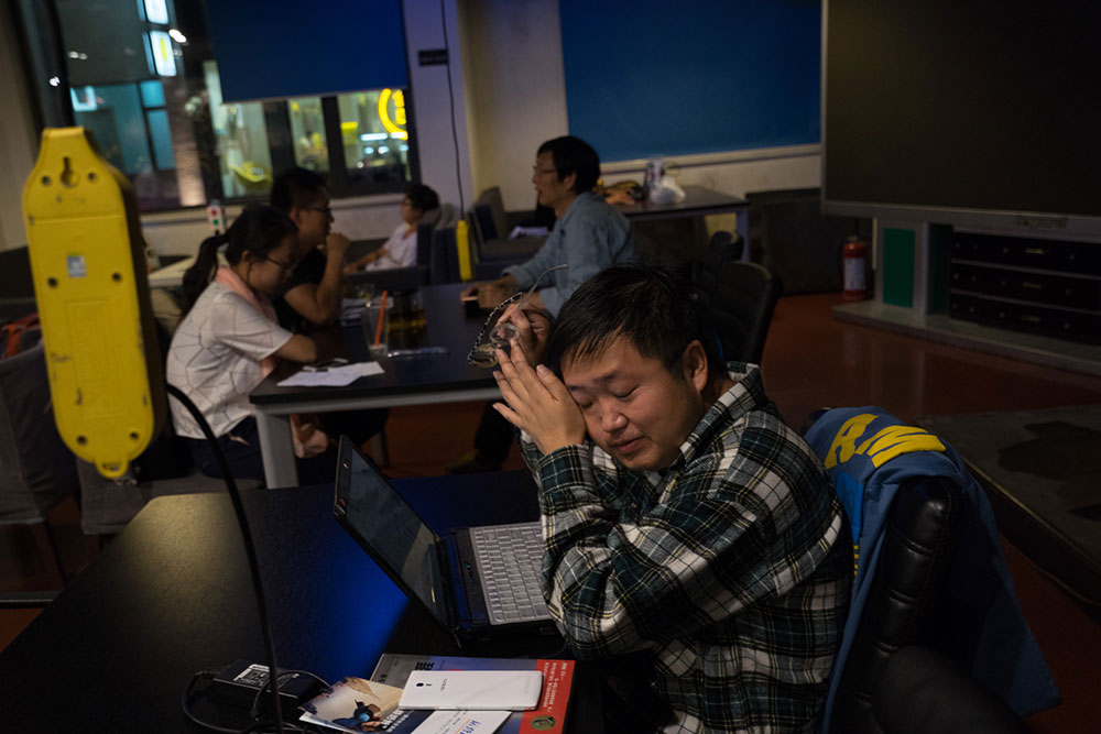 Working at The Garage, Wu takes off his glasses to massage his eyes. One often sees grassroots entrepreneurs here pacing around and waiting; they think of The Garage not just as a space to work, but also as a platform on which to interact with other entrepreneurs, find partners, or find investors. (Photo by Yan Cong)