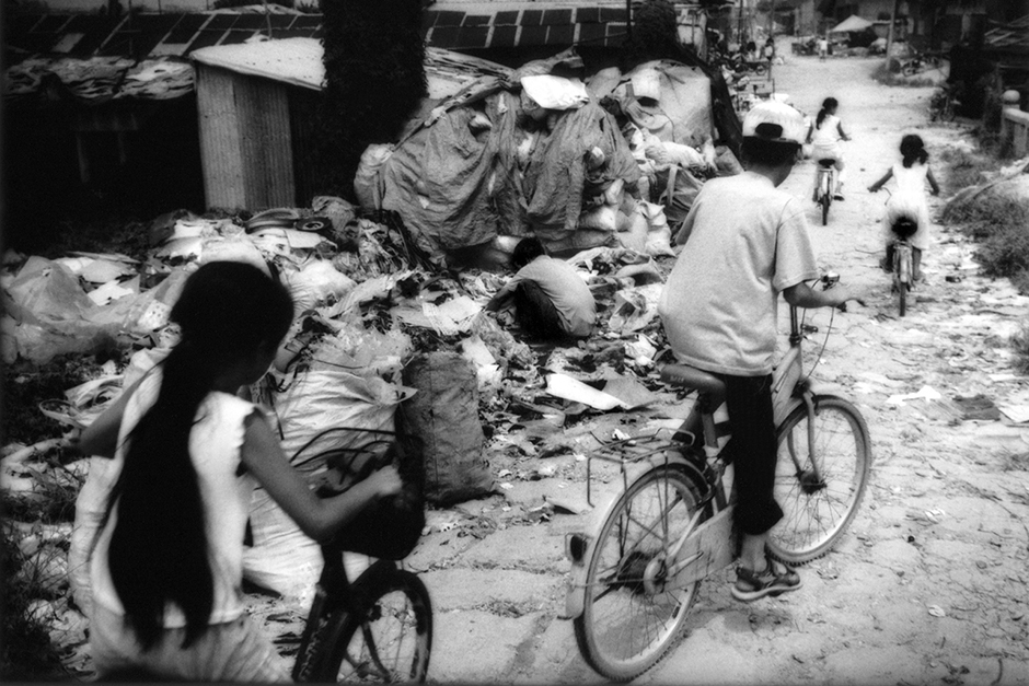 Children ride past computer components, imported from North America, Europe, and Japan. The parts, many of which are toxic, are dismantled and their recyclable materials extracted for sale in what was, less than a generation ago, a bucolic agricultural village outside of Guiyu, Guangdong.