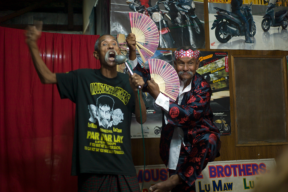 "The Moustache Brothers perform their famed and blacklisted comedy act, which makes China as well as the Burmese government the butt of many jokes. As performer Par Par Lay, right, does a mock Chinese dance, his younger brother Lu Maw, left, says: ""Burma is very lucky to have China as a neighbor. We can have Adidas, Nike. Only three dollars. All fake."""
