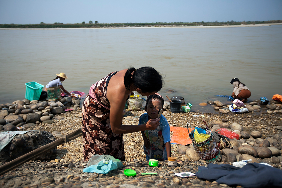 On the languid shores of the Irrawaddy River, a Burmese woman brushes <em>thanaka</em>, a traditional sunblock powder, on her son's face after a mid-day bath. Though currently on hold, the Myitsone dam project threatens to alter life in riverside towns. The Chinese-financed hydroelectric project was suspended in September 2011 after years of public outcry.