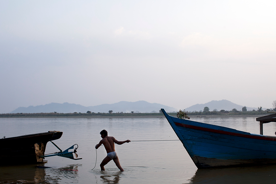 A man hauls his boat from the shore in the early morning in Myitkyina, the capital of Kachin State. If the Chinese-financed Myitsone dam project is ever completed, this area—some 120 square miles—will be flooded.