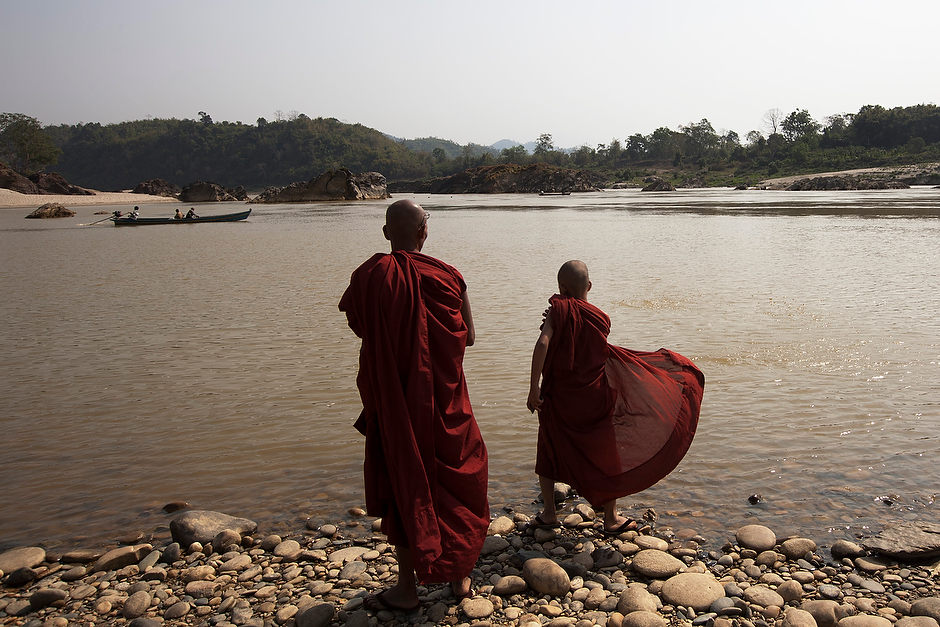 Monks stand at the edge of the confluence waters of the Mali and N'Mai Rivers.