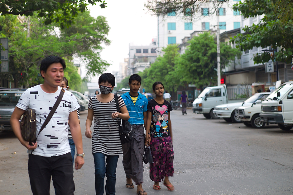 Mainland Chinese walk on the streets of Mandalay, their clothing and demeanor identifying them as foreign.