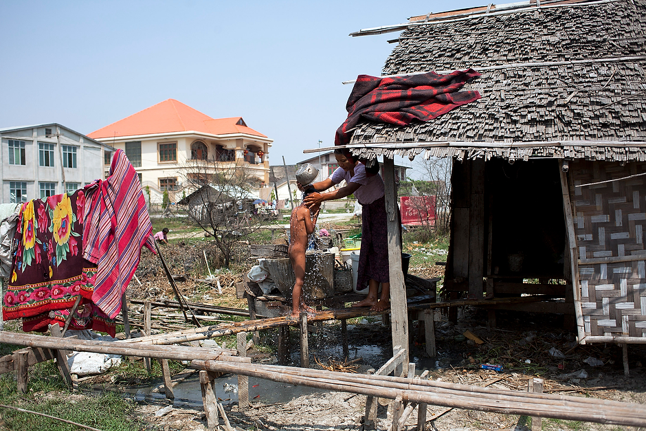 Ngwe Nyi Aye bathes her child, Naing Min Tun, 6, at their shack on the outskirts of downtown Mandalay, in view of a villa owned by a Chinese family.