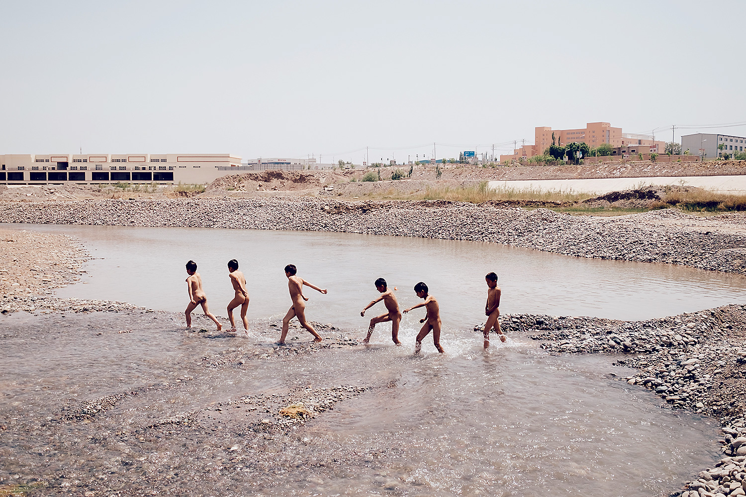 Children run through the Tailiwei Quke River in Guangzhou New City, Kashgar. New links with Guangdong are spurring growth in this arid region, formerly an oasis on the old Silk Road trade route. The New City takes its name from Guangdong's capital, Guangzhou.