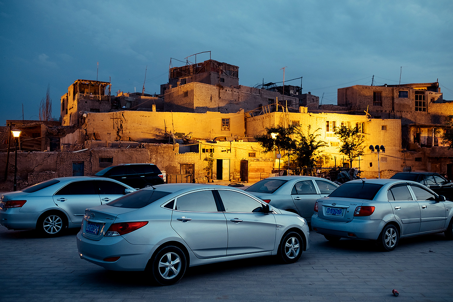 On the edge of the Taklamakan Desert, modern automobiles sit in the shadow of a bazaar in the Old City on a warm spring night. In 2009, Beijing promised improved living conditions for city residents and a new, updated Old City for tourists.