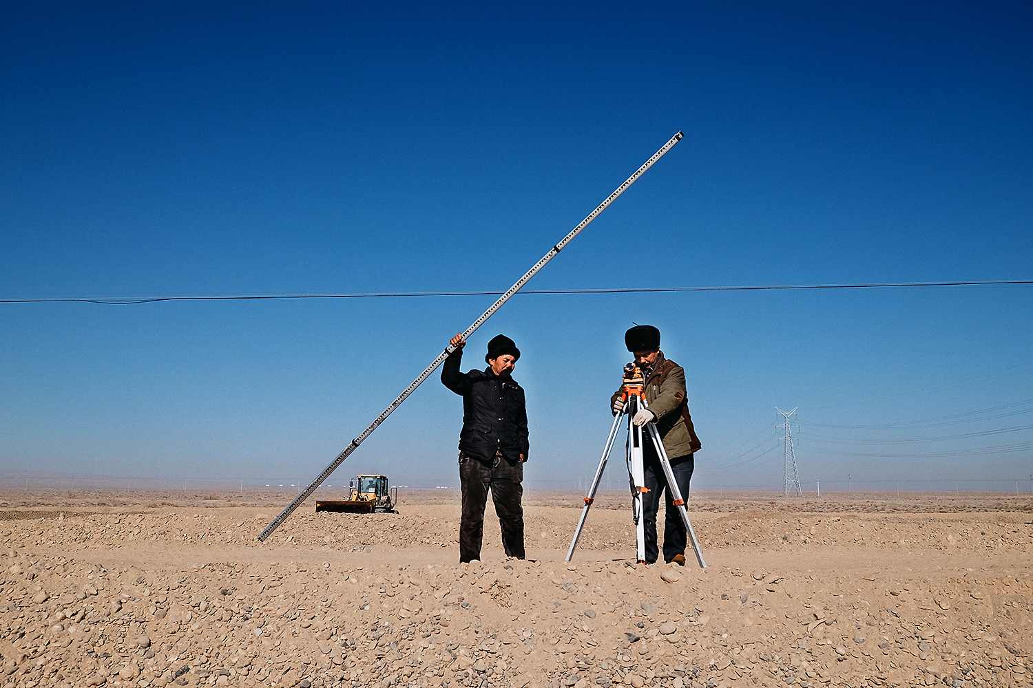Uighur surveyors measure the future site for a green space near a planned station on a new railroad to Central Asia.