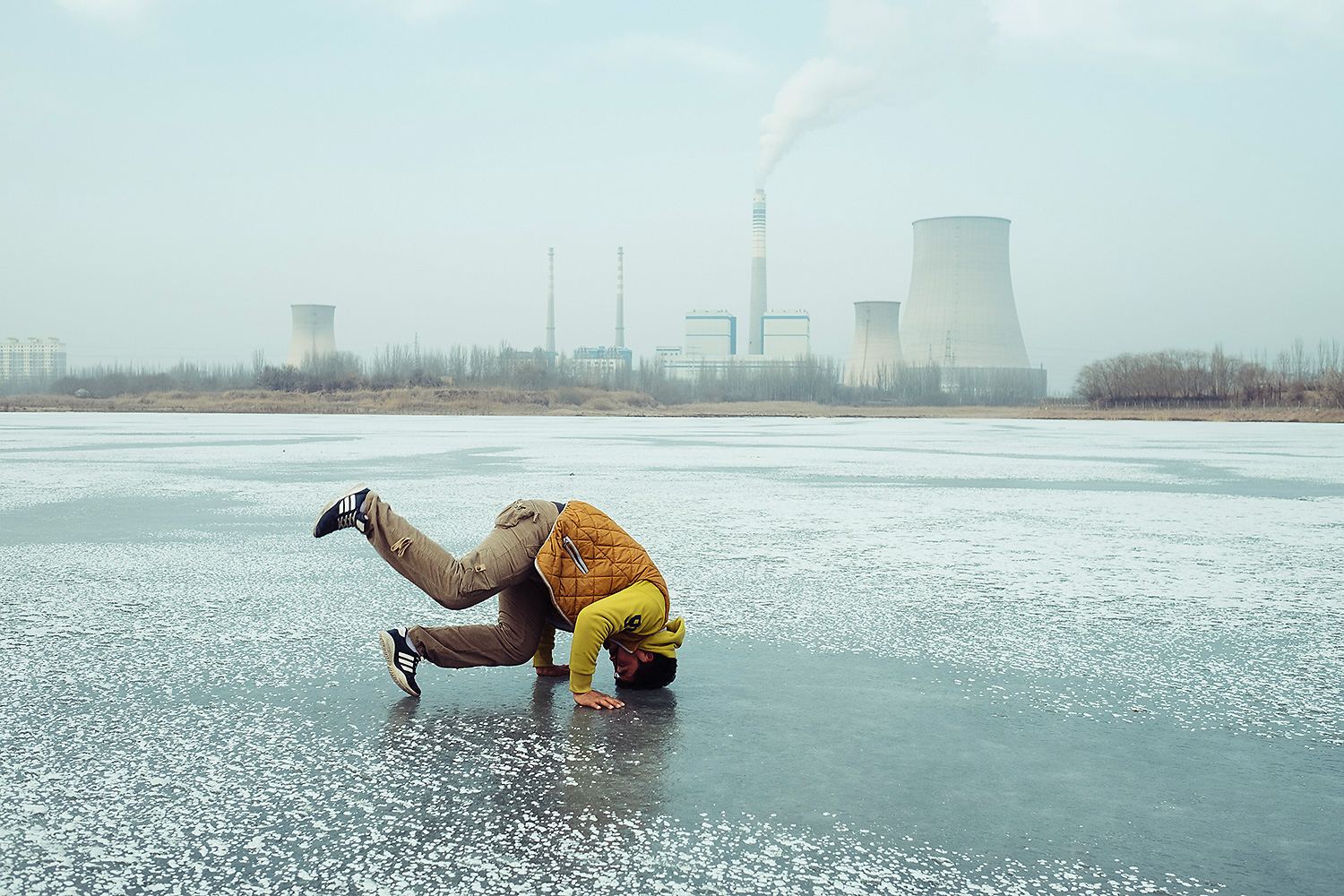 A young man attempts a head stand on the frozen Xiaoyalang Reservoir near a thermal power station.