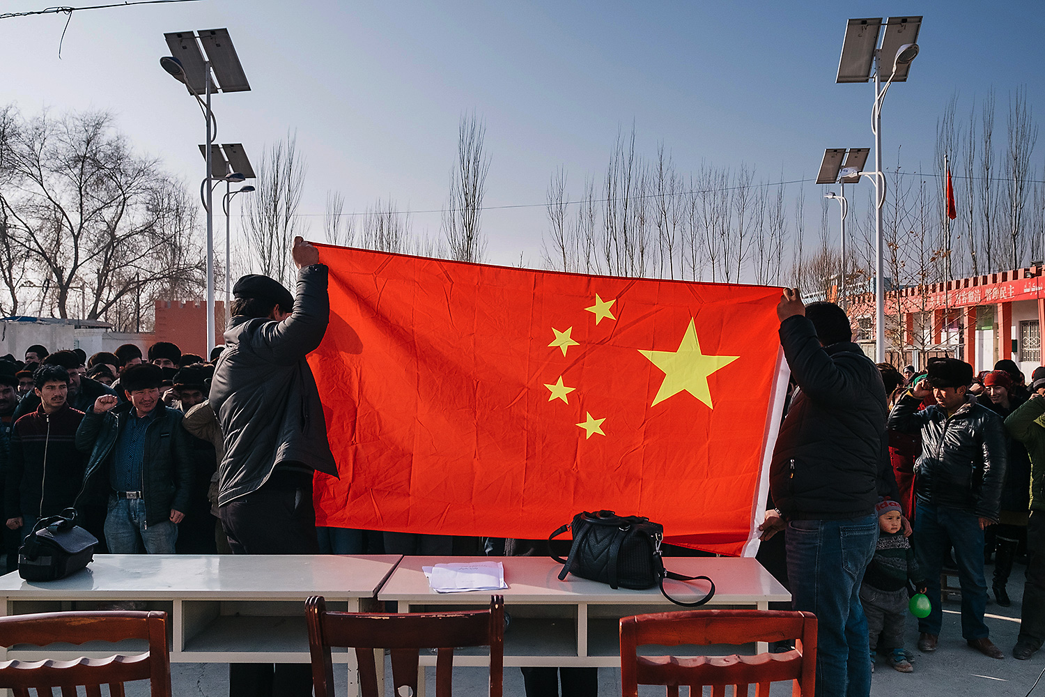 Uighur villagers pledge their allegiance to the People's Republic of China, and its flag, during a weekly meeting led by Party cadres as part of an effort to dampen separatism in the region.