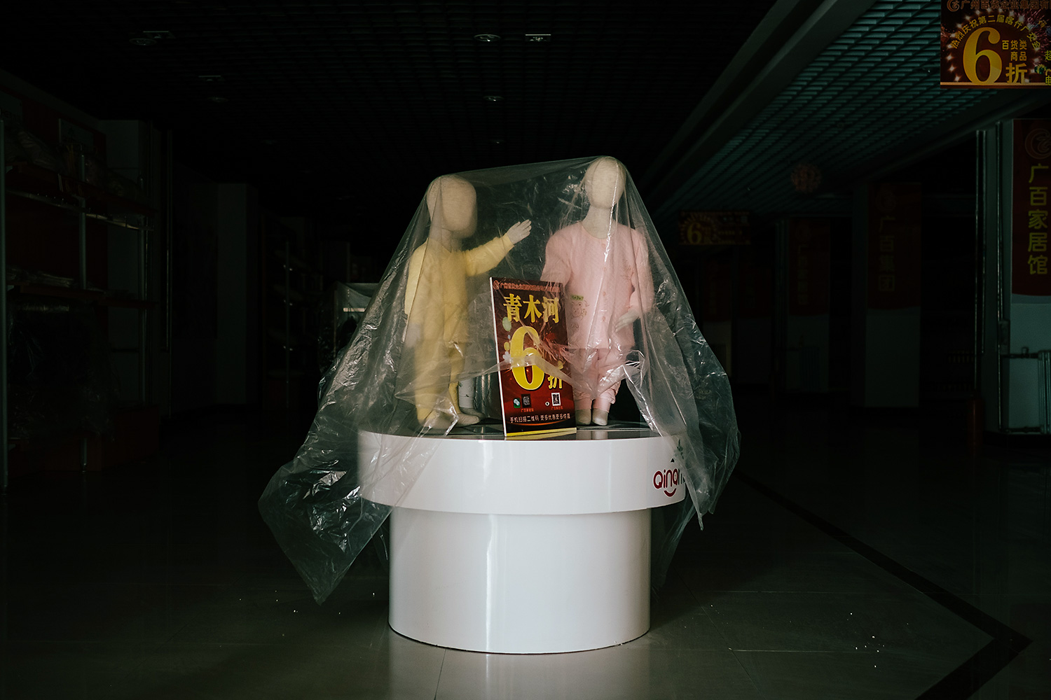 A plastic covering protects these child-sized mannequins from desert sand at the T.I.T. Lifestyle Store, opened by a textile company from Guangzhou.