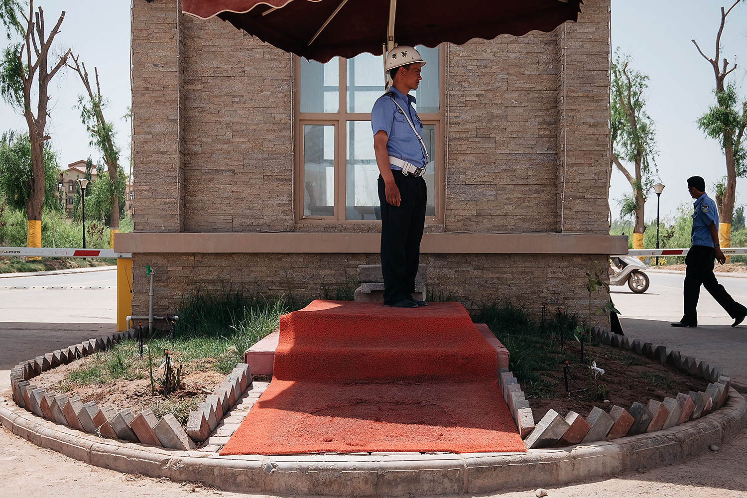 Uighur guards patrol an entrance gate of the South Xinjiang Venice villa district, which caters to wealthy residents, many of whom are Han.
