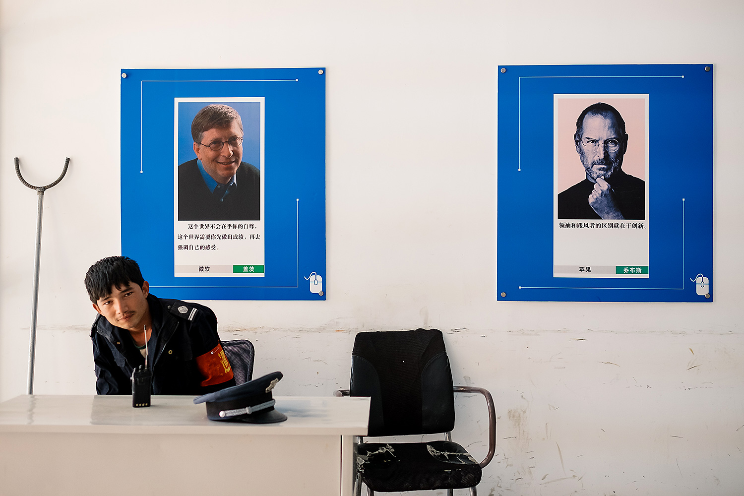 A guard rests below inspirational posters of Microsoft's Bill Gates and Apple's Steve Jobs at the Kashgar E-commerce Headquarters Base of West China, a government incubator.