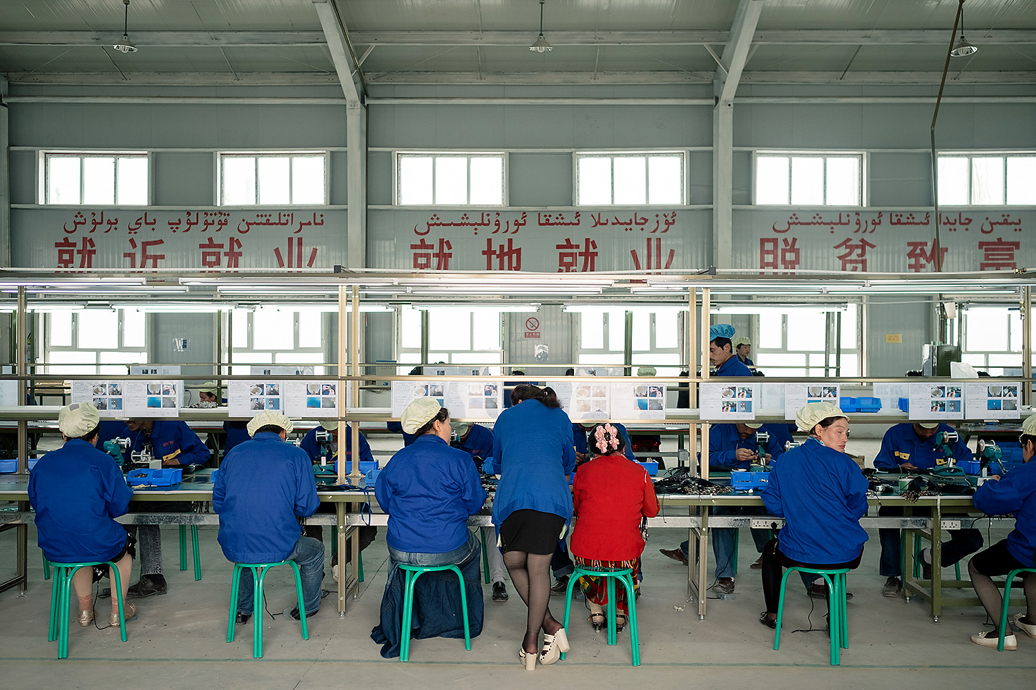 Uighur workers labor at the Guangdong Sike Electronics factory, where local workers earn a monthly salary of 1,500-2,000 yuan (U.S.$200-300)—up to three times more than the average income in nearby villages, and slightly more than the average income in the city of Kashgar.