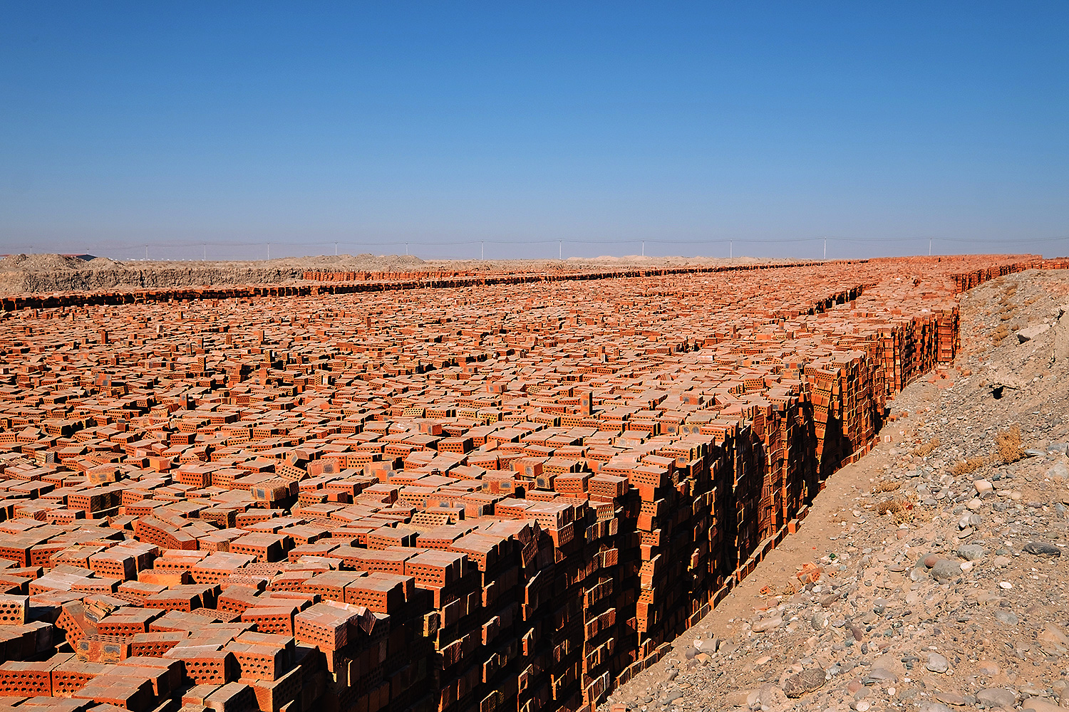 Bricks for sale stand in piles outside of a future industrial park.