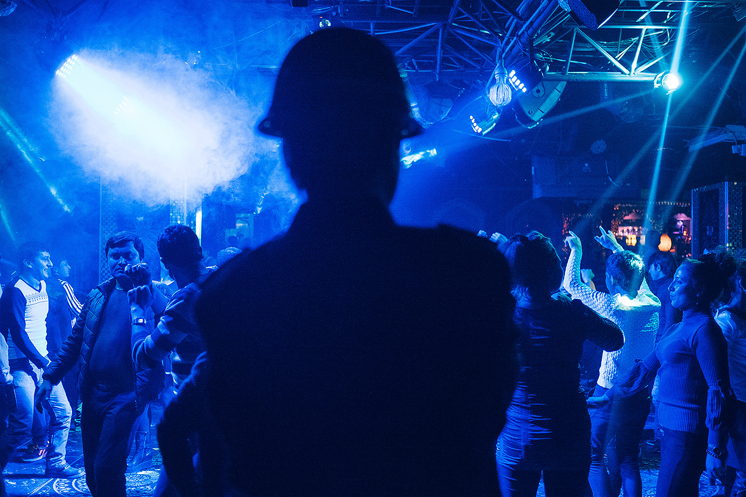 Revelers dance under the surveillance of security guards after midnight at a local club.