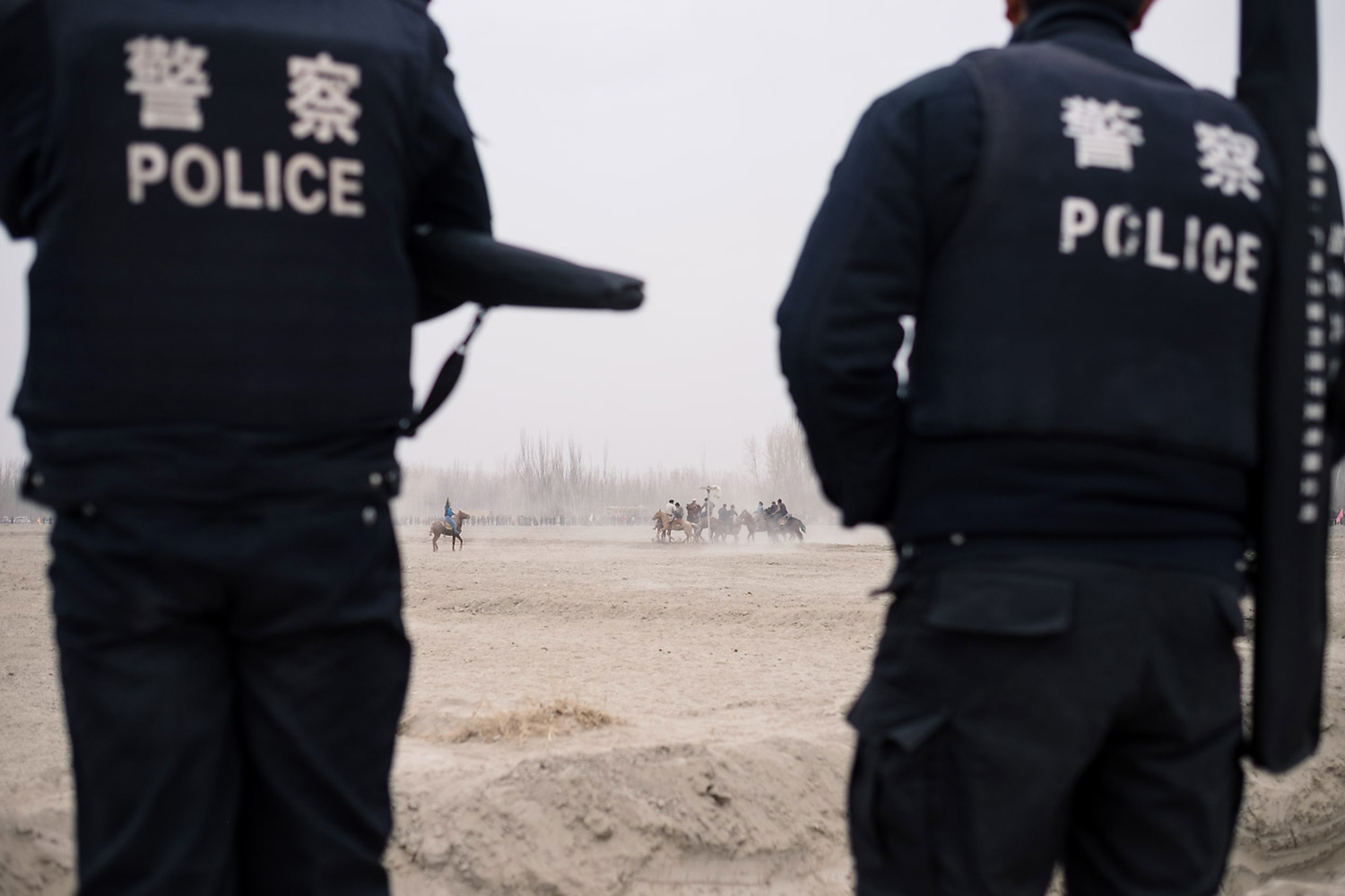 Police officers stand on duty at a horse race in a village near Kashgar.