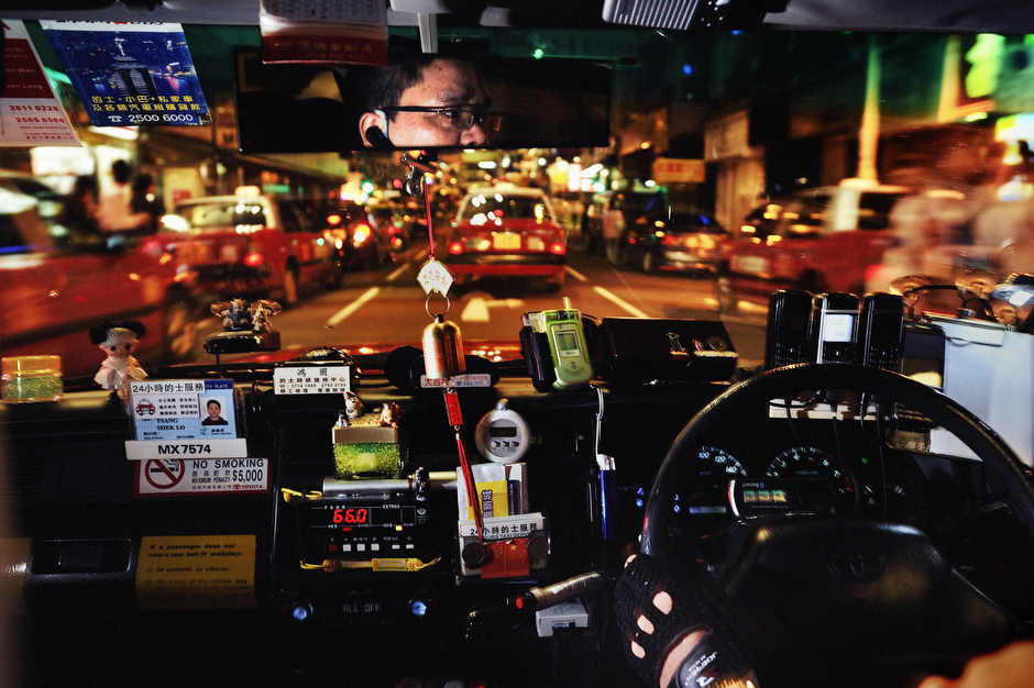 "The dashboard of a ""discount taxi"" displays trinkets, charms, official placards, and several extra mobile phones mounted in view, connecting the driver to various dispatching syndicates who book discount long-haul fares to undercut the traditional first-come-first-serve rule."