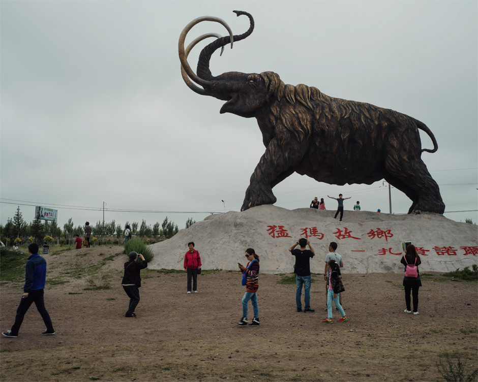 Tourists visit a wooly mammoth statue, built to commemorate a fossil discovery, in Mammoth Park in the Jalainur district of Manzhouli.