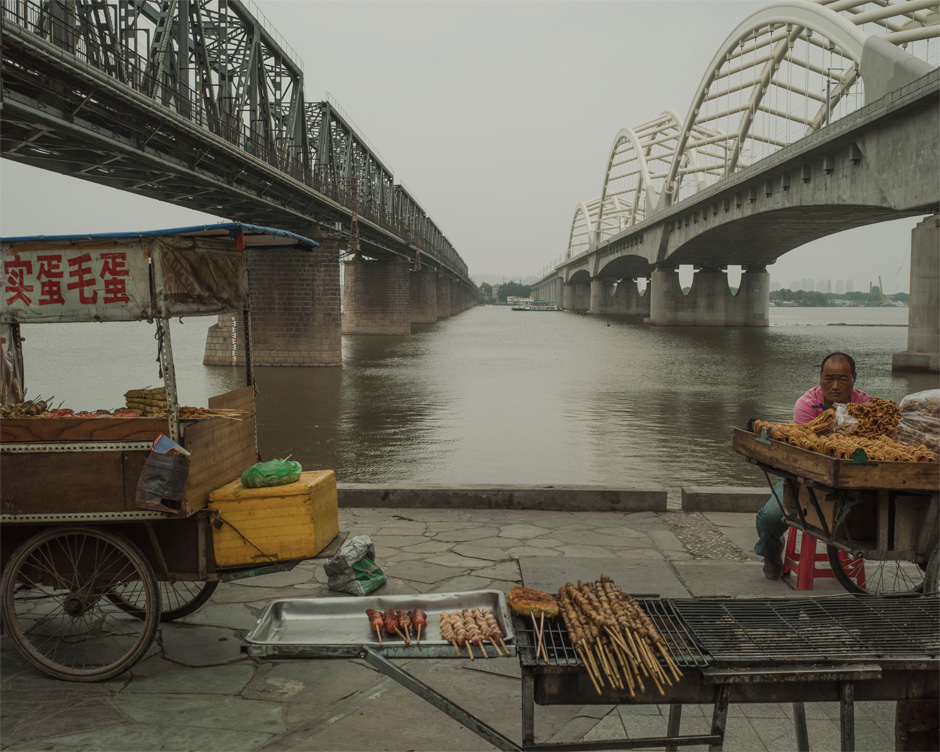 A food vendor awaits customers on the bank of the Songhua River in Harbin, beneath bridges used by Chinese Eastern Railway. Chinese in name alone, the railway was built on a strip of land controlled by Russia that was exempt from the jurisdiction of local Chinese law in a deal brokered between the two countries after China lost the Sino-Japanese war. The old bridge, seen at left, was built by the Russians at the beginning of the 20th century; the newer one was built by the Chinese.