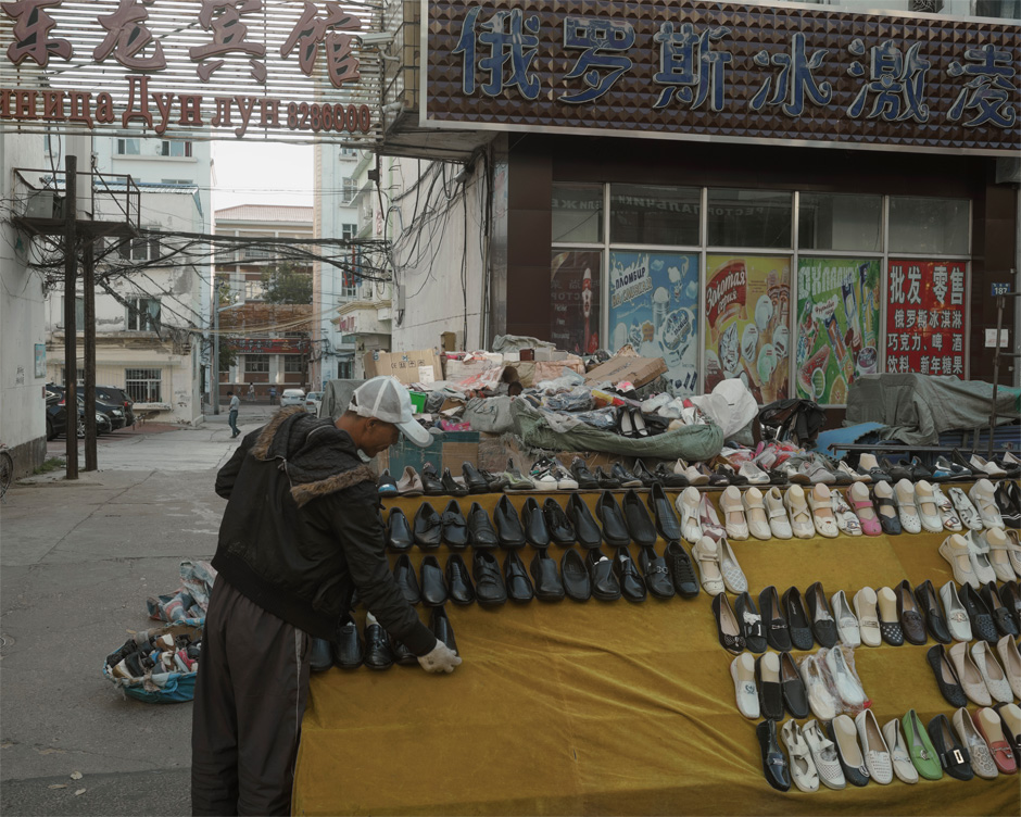 A shoe peddler sets up his wares in the city center of Heihe where the city street transforms into a huge market for Russian customers arriving from Blagoveshchensk, across the Amur River. Until a decade or so ago, it was a rural backwater, but a special economic zone was established in the city in the mid-90s, and the city has since grown to a population of close to 2 million.