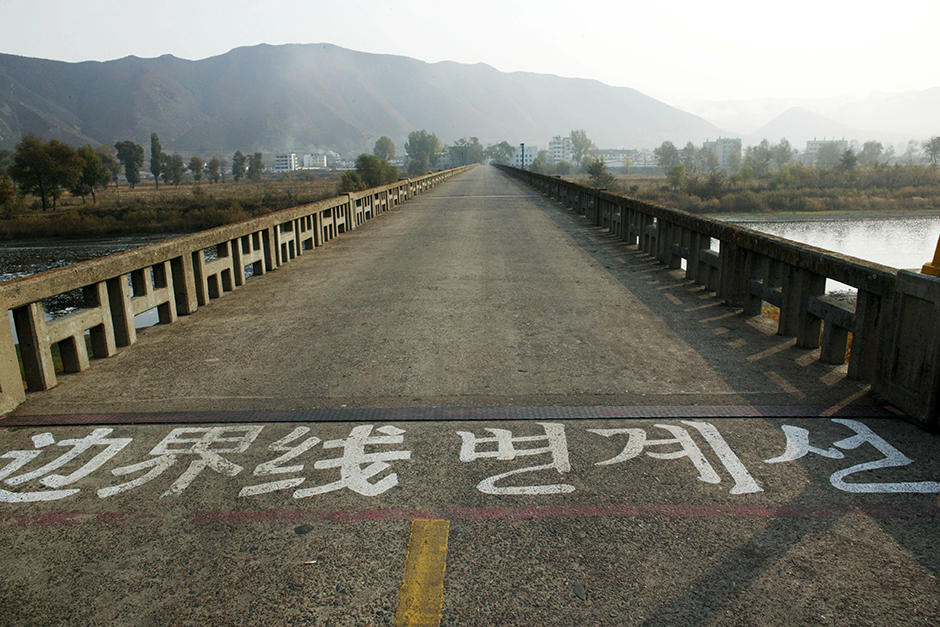 The yellow traffic-line paint stops mid-bridge at the official demarcation line in the Tumen border area that separates China and North Korea, seen in the distance, October 2008. While this bridge often facilitates trade, it is also used as a channel to return refugees caught in China.