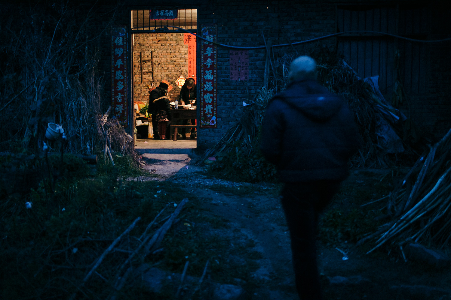 Li Mingjin walks toward his home as his 68-year-old mother and his wife prepare dinner, in Longjing village, March 5, 2015. According to Mingjin, he and his wife told his mother that his disease was not serious and could be easily treated. They wanted to prevent her from worrying too much.