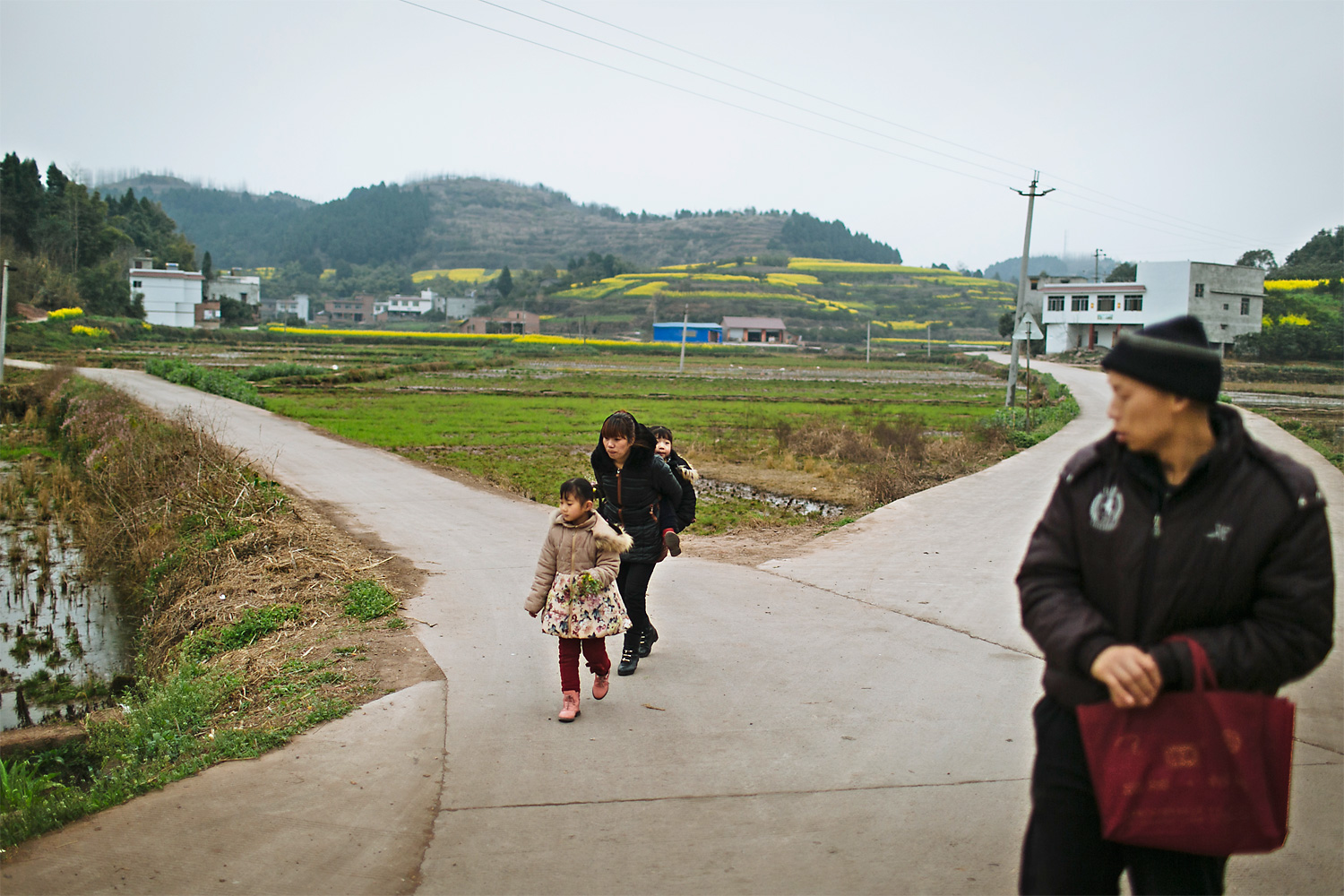 Li Mingjin looks at his wife, Ning Xianfang, and their two daughters as they walk towards home, in Longjing village, March 6, 2015. After Mingjin got sick, Xianfang had to take care of the whole family. She doesn't have time to work and Mingjin is not able to work, so the family doesn't have any income.