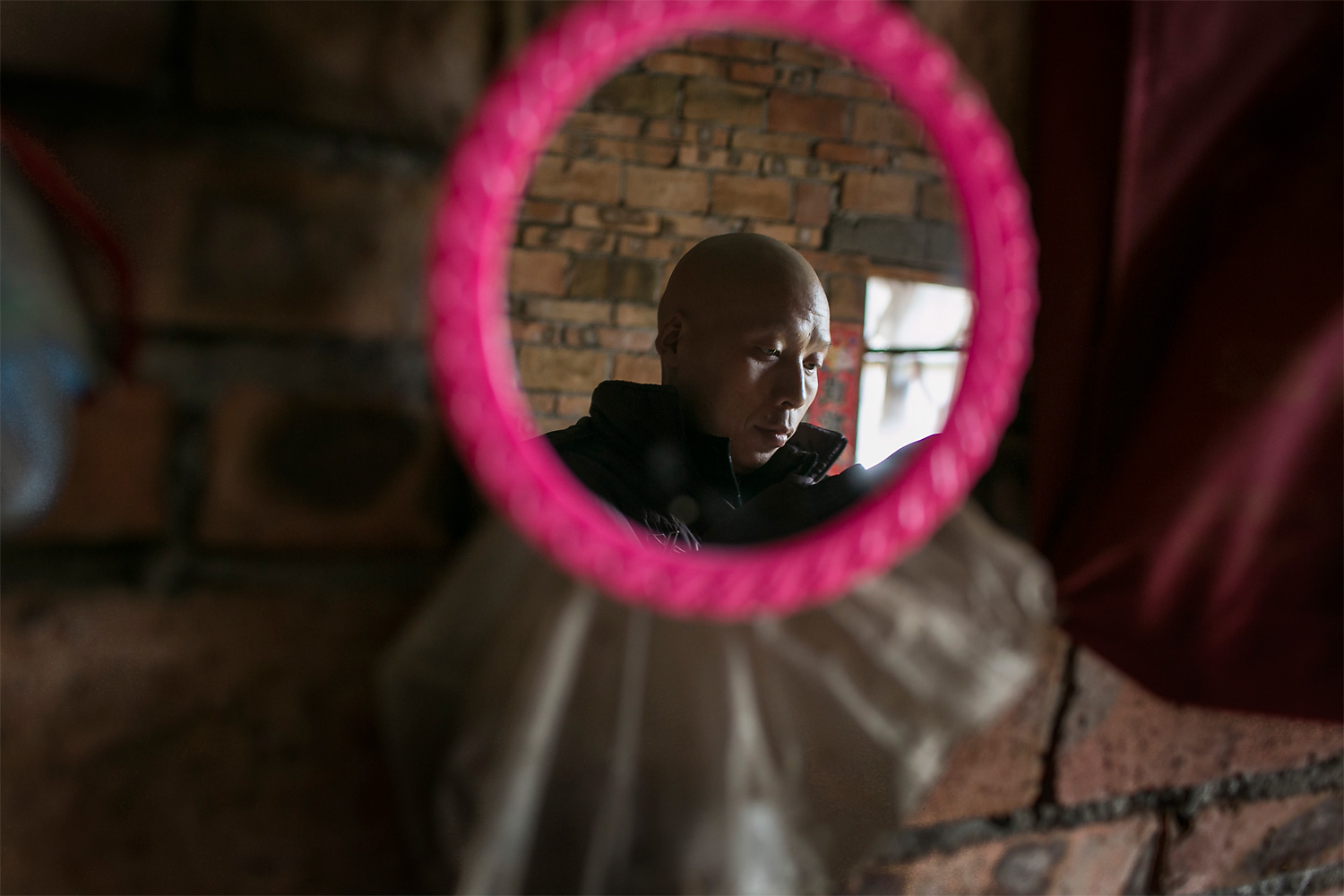 Li Mingjin puts on his hat in front a mirror at home, in Longjing village. He shaved his head because of the chemotherapy. In winter, he feels cold without hair, so he always wears a hat. Mingjin had worked as a miner in Shanxi province for 19 years, but in November 2014 he was diagnosed with lung cancer.