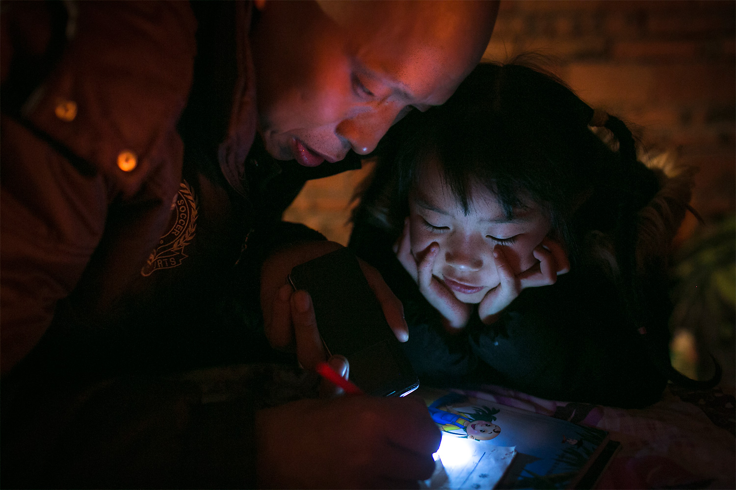 Unable to afford to send his daughters to school, Li Mingjin teaches Siyao writing at night by the light of his cellphone, at home, in Longjing village.