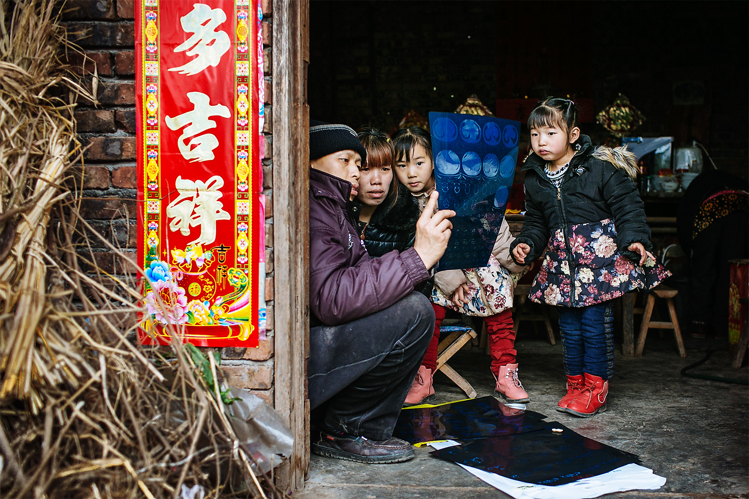 "Members of the family gather to look at Li Mingjin's CT scans. The trial treatment he received in Beijing had a positive effect, the doctors said, but after the free trial was over, the family couldn't afford to continue treatment. The Chinese characters on the wall read ""more luck."""
