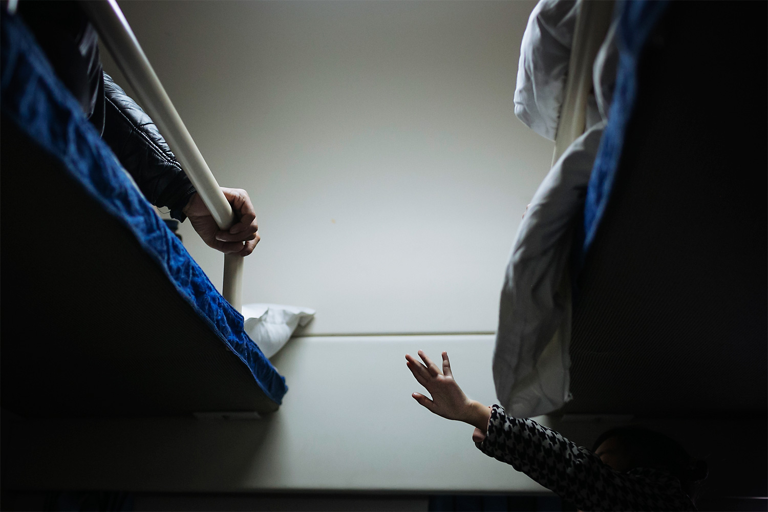 On a return train bound for Chengdu, Sichuan province, Siyao reaches out to her father to touch his hand as Li Mingjin lies on the bed gripping the edge tightly because of pain.
