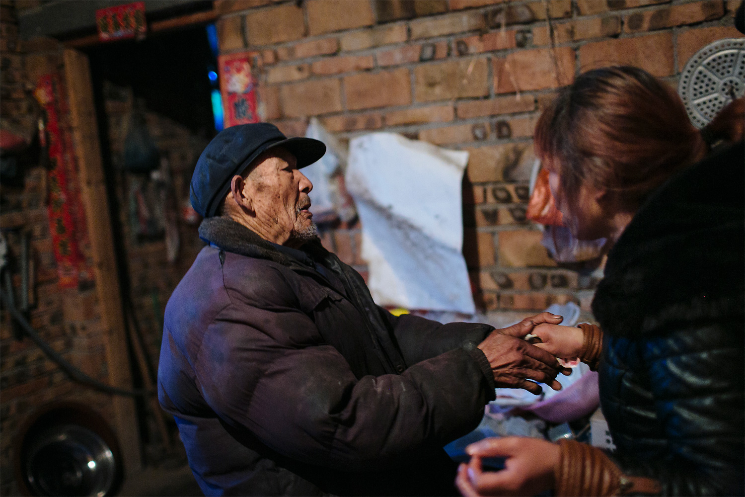 A village elder pays the family a visit and gives Ning Xianfang 160 renminbi (U.S.$25), nearly all of his 200 renminbi monthly income.