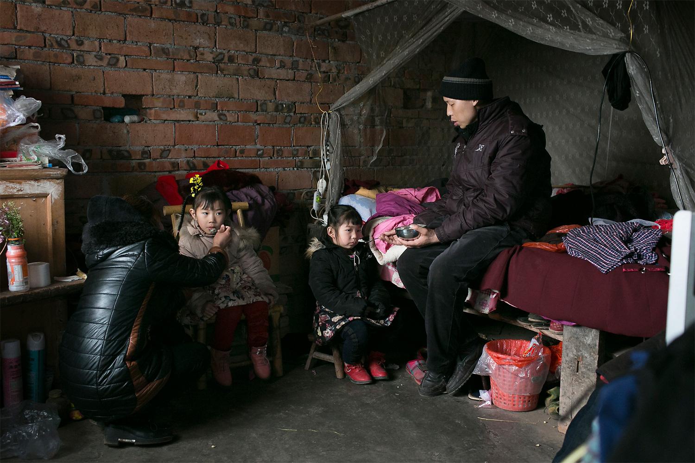 Li Mingjin and Ning Xianfang feed their daughters breakfast while the children watch morning cartoons.