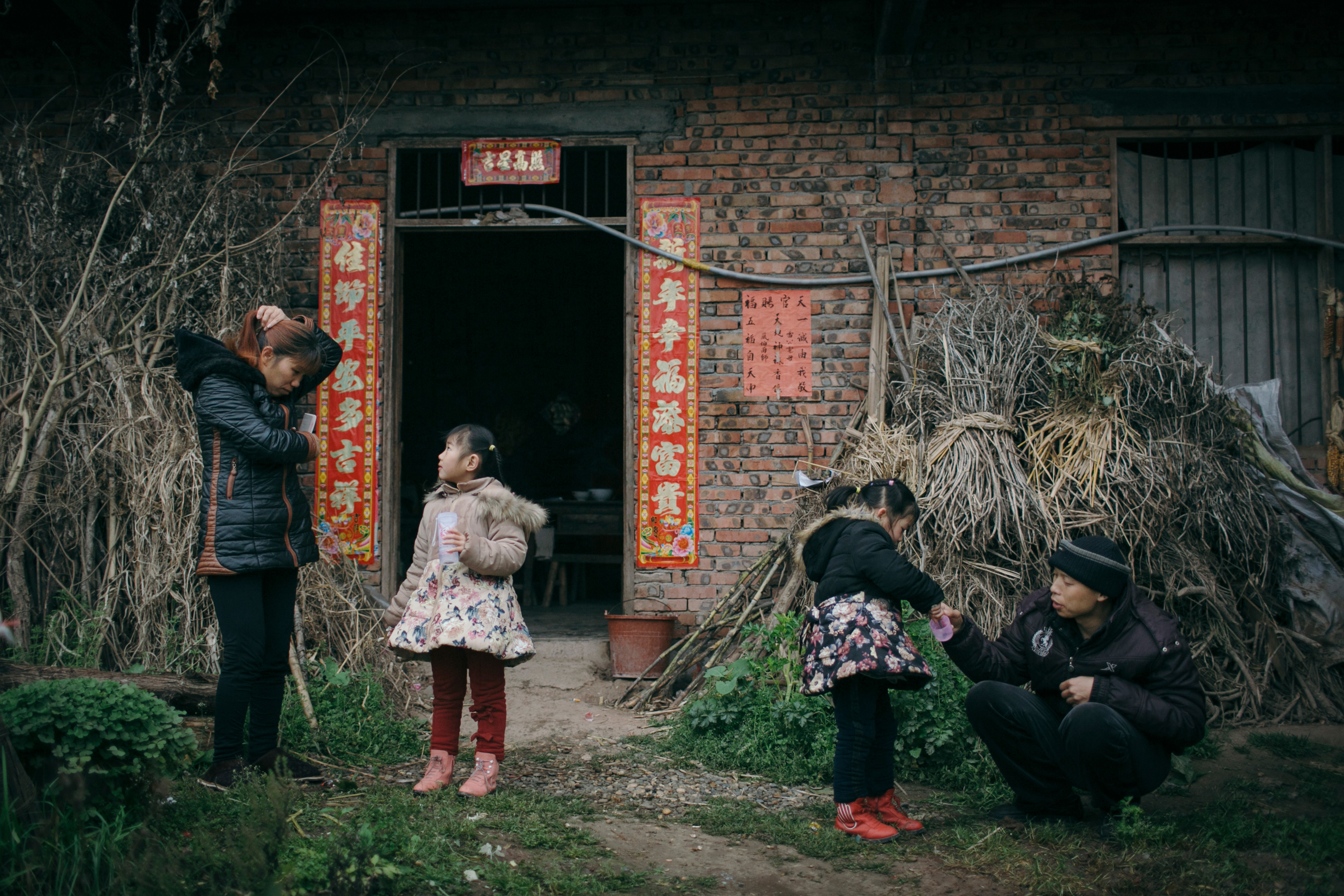 Li Mingjin and Ning Xianfang monitor and help Siyao and Mengmeng brush their teeth, in front of their home in Longjing village, March 6, 2015.