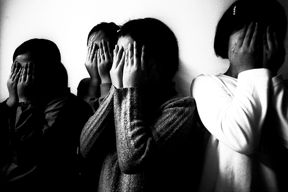 Four North Korean teenage girls, who fled their native country in 2001, hide their identities in a farmhouse near the North Korean border, January 2003.