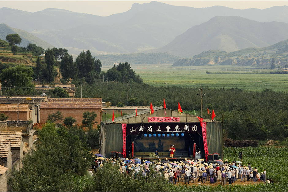 Erected on the edge of a village, the performance stage stands in a field cleared of the year's crop of corn. The troupe has settled in for two days of performances here in the mountains of Xiyang County, Shanxi. The lead singer is from this village, so the troupe has offered to perform for free. Otherwise, the villagers here likely would not be able to afford such a prominent troupe.
