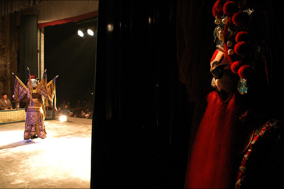 A Sanjin performer watches from offstage awaiting his entrance. Many of the performers enter this life at an early age—a life full of long travel, financial hardship, and few amenities. Their audiences are rarely aware of their lives off-stage and and expect the same high-quality and entertaining performance every time.