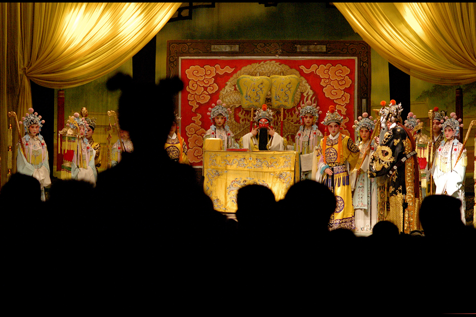 In a packed audience, children sit on adults' shoulders for a better view. Children and the elderly make up most of the audience for these traveling opera performances. Young adults have largely turned away from traditional Chinese opera, as few appreciate the subtleties of this difficult-to-understand art form.