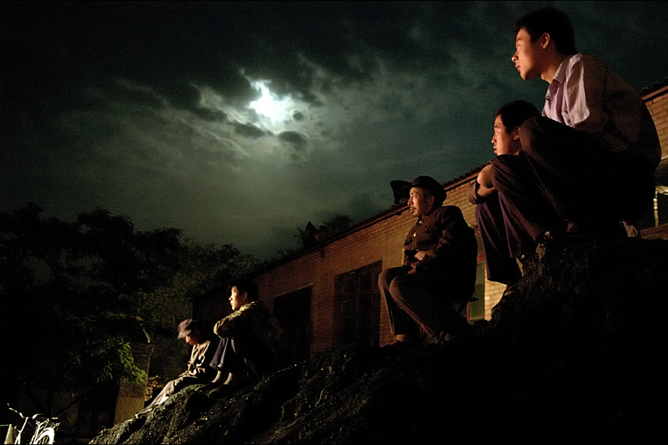Piles of coal serve as box seats for the overflow audience as moonlight mixes with the warm glow of stage lighting during an evening performance. Shanxi is a coal-rich region, and the owner of the troupe owns a coal mine. Profits from this venture provided the resources to found the troupe.