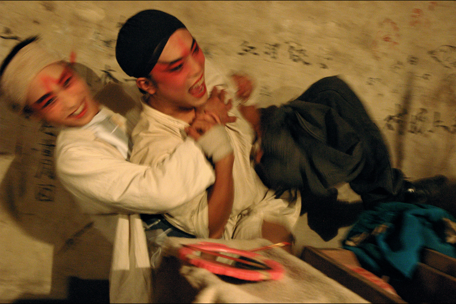 Backstage after a matinee performance, Guo Shenghai and Qin (with black headband) horse around during the few hours before the more popular evening performance begins. Despite the levity, Qin's past is marked with sorrow: After ten years with the troupe, he left, but then lost his life savings in a pyramid scheme. His friends in the troupe loaned Qin money for train fare so he could join them on the road again.