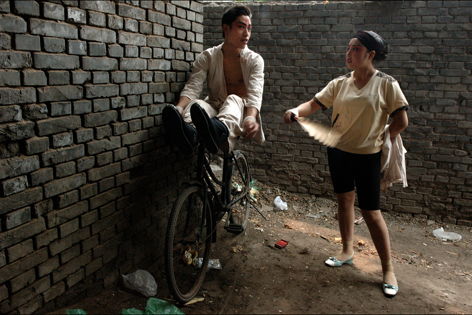 Ninteen-year-old Guo Shenghai chats with a girlfriend during a play. The shows usually last three to four hours, and the performers must pass the time in between in makeup. Guo joined the troupe when he was fifteen. Coming from a farmer's family, he discovered opera  at the age of eight when a traveling troupe came to his village. Fascinated by the mix of colors, music, and martial arts, he soon joined an opera school. He now mostly plays the role of a soldier, a role that allow him to display his skills at kung fu.