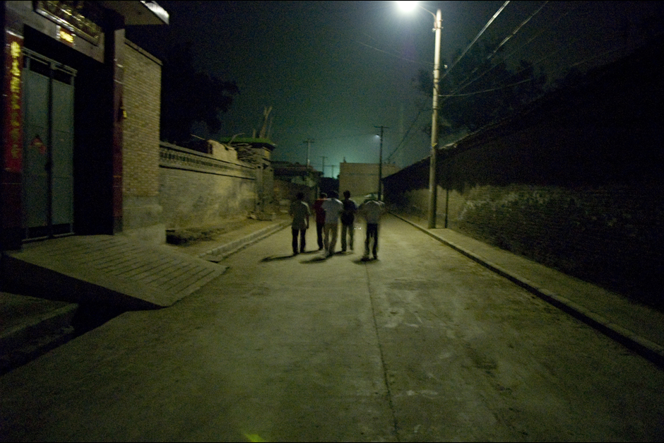 Friends and performers walk through empty streets late at night in the village. Without their costumes and makeup, these generals, heroes, traitors, and villains retreat into the darkness, only to perform again the following day.