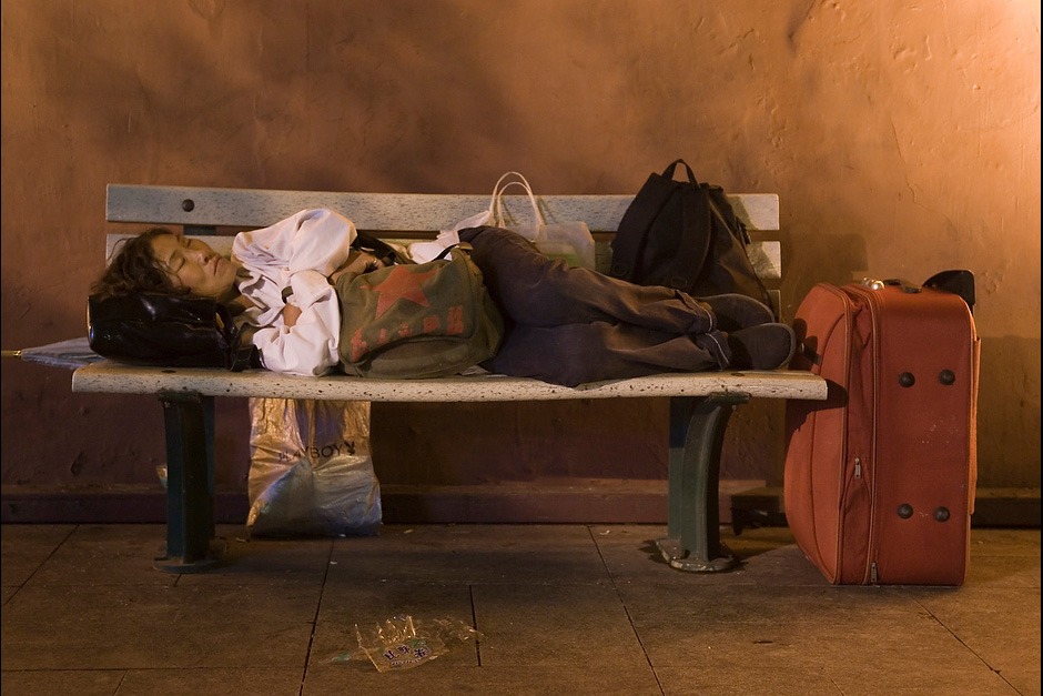 A migrant worker sleeps on a bench in Beijing, China. During summer nights, on Chang'an Jie near Tiananmen Square, the benches are occupied by tourists, the city's homeless, migrant-workers, and many others who spend the night.