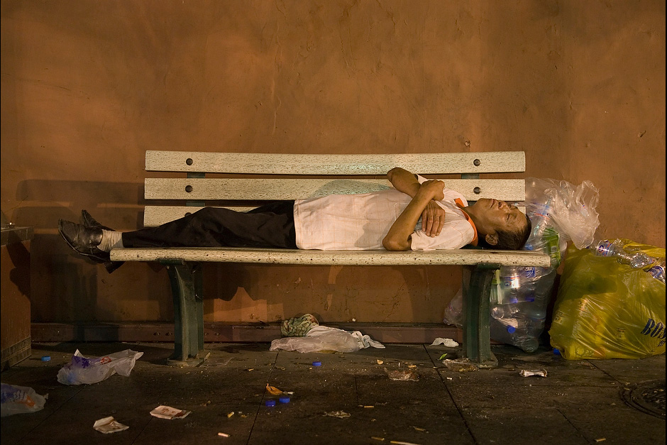 A garbage collector sleeps on a bench next to a collection of plastic bottles that he will exchange for income at one of Beijing's recycling collection centers.