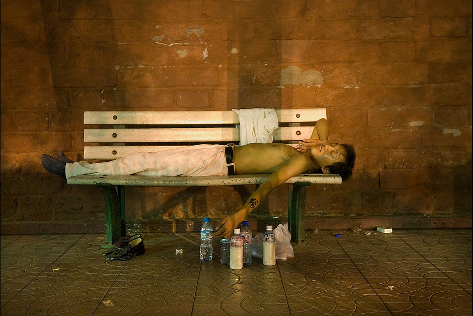 "A man sleeps on one of the benches, the character for ""fate"" written on his forearm."