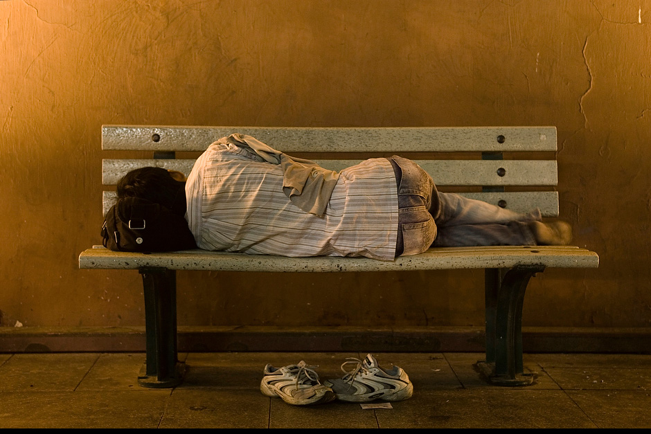 Using his jacket as a blanket and his bag as a pillow, a man sleeps on a bench.