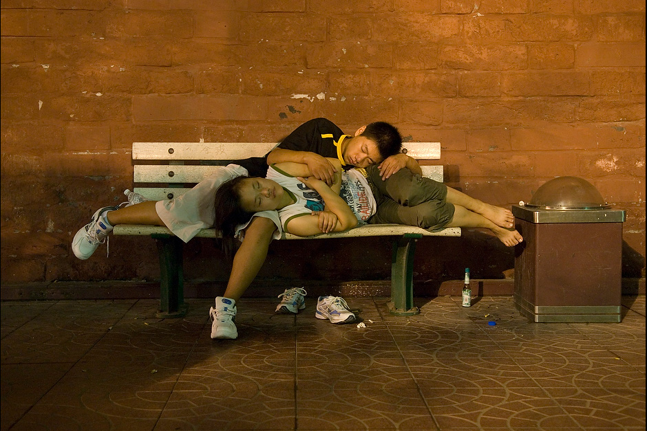 A teenage couple sleeps on a bench using each another as cushions.