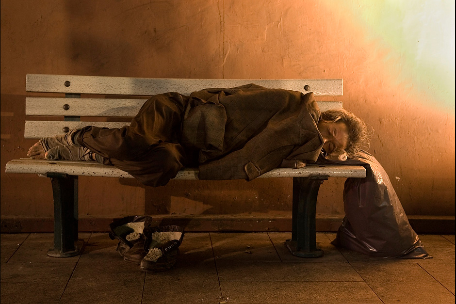 Wrapped in a jacket, a homeless man sleeps on a bench.